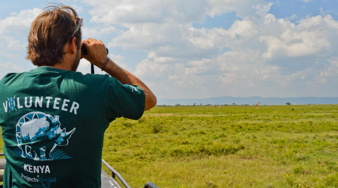 A volunteer in Kenya monitors the giraffe population during an African conservation experience abroad